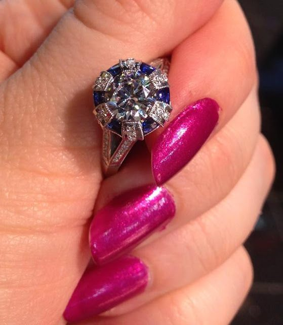 Art Deco inspired Tacori engagement ring with a center diamond and diamond and sapphire accents. Via Diamonds in the Library.