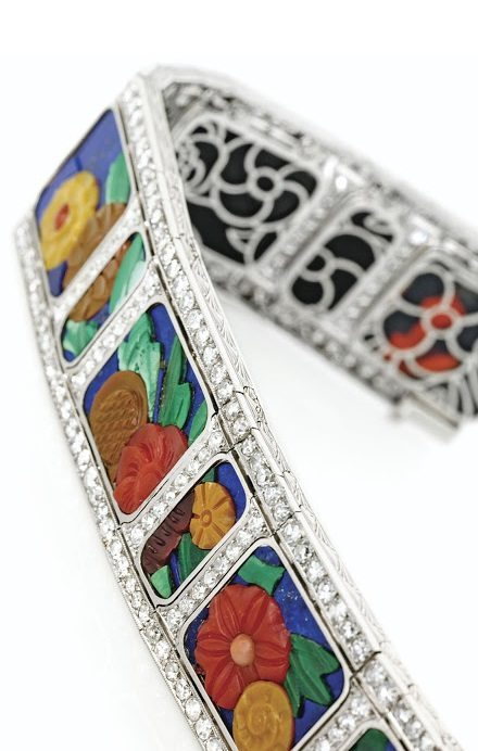 An Art Deco carved hardstone and diamond bracelet with diamonds, coral, carnelian, chalcedony, malachite and lapis lazuli. Circa 1925.