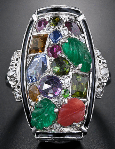 A Tutti-frutti Art Deco dinner ring, circa 1925. An unusual design incorporating carved emeralds, sapphires, rubies, amethysts, citrines, and diamonds within a border of black enamel.