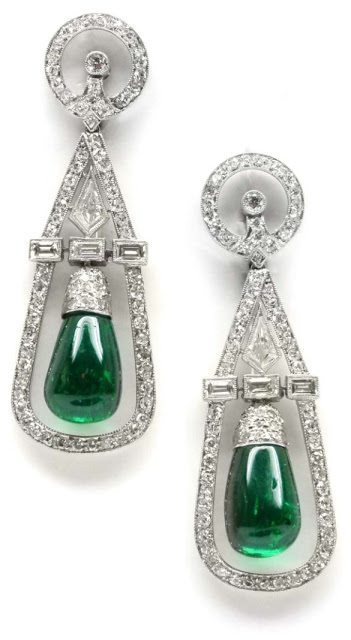 Art Deco emerald and diamond earrings by Cartier, circa 1935. Each earring is hung with a polished emerald within an open diamond-set frame.