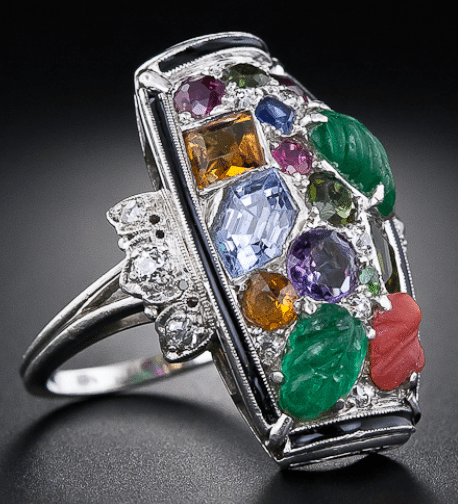 Side view; Tutti-frutti Art Deco dinner ring, circa 1925. An unusual design with carved emeralds, sapphires, rubies, amethysts, citrines, and diamonds within a border of black enamel.