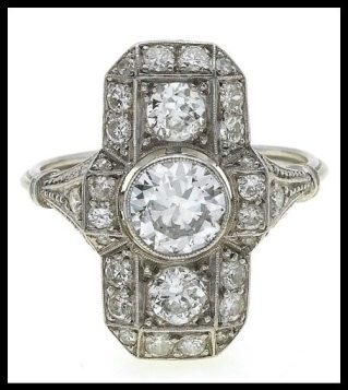 Art Deco platinum and diamond cluster ring from the 1930's, featuring one large diamond flanked by two slightly smaller ones and set into a diamond-enhanced plaque. Via Diamonds in the Library.