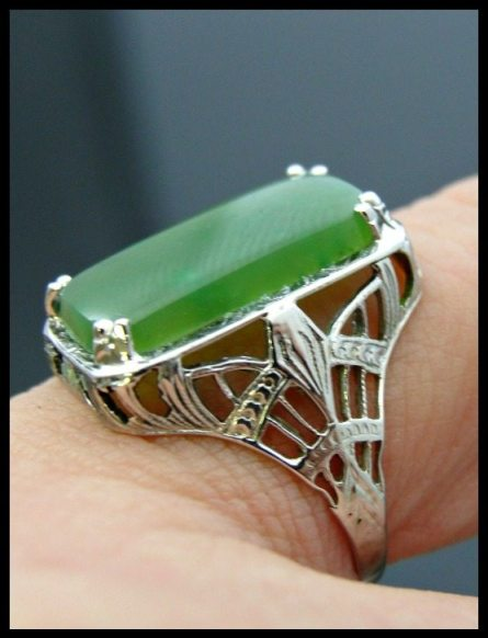 Art Deco white gold filigree ring with green jade. Via Diamonds in the Library.