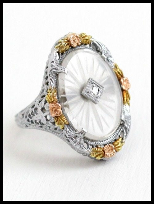 Antique Art Deco camphor glass, three-color gold, and diamond ring with filigree and floral details.