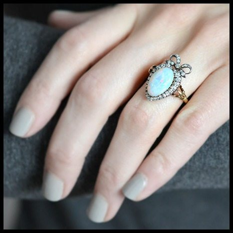Victorian opal and diamond ring in 18k silver-topped-gold heart setting with a diamond-set bow; on a hand