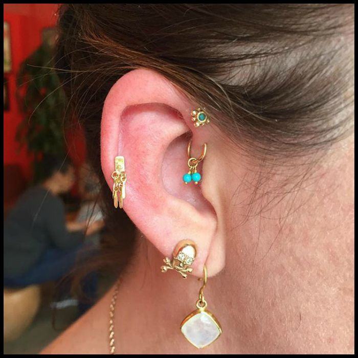 An assortment of gold ear piercings on Alyssa of The Jewelry Altar; photo and piercings by @cassisoclassy (on Instagram).