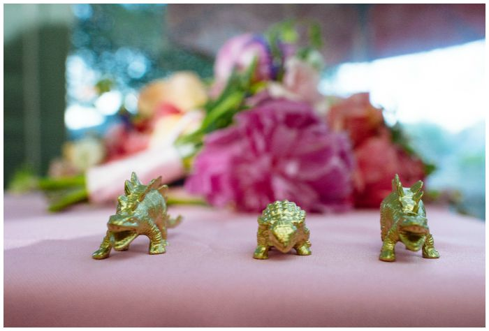 Pink flowers and tiny golden dinosaurs at our wedding reception. Photography by Angel Kidwell.