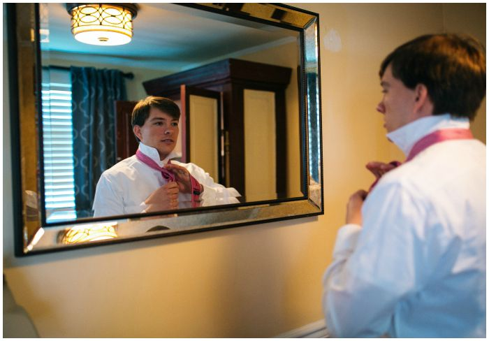 The tying of the groomal tie! An important moment Photography by Angel Kidwell.
