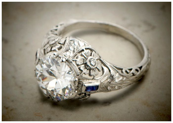 An antique engagement ring with a 2.46 ct diamond in platinum. Floral and sapphire details. Edwardian, circa 1920s.