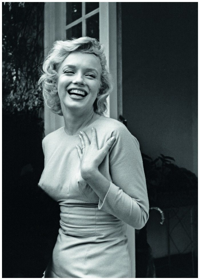 A smiling Marilyn Monroe, wearing her diamond eternity band engagement ring from Joe DiMaggio, 1956.