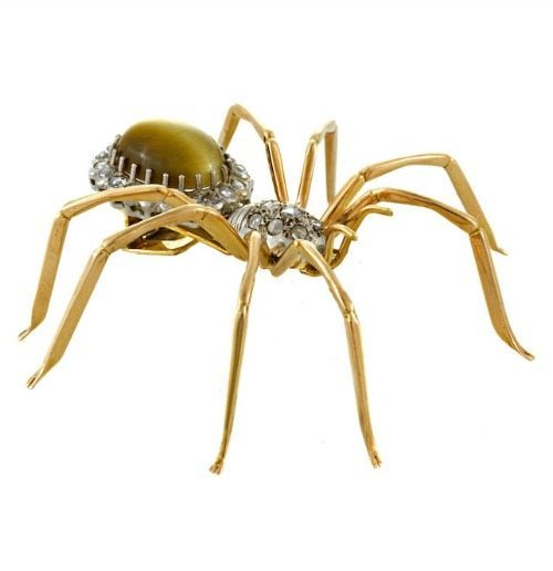 A spider brooch in gold with a tiger's eye body and diamond embellishments. Sold at Bonhams.