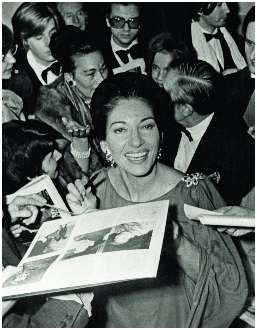 Famous opera singer Maria Callas wearing her ruby and diamond Van Cleef & Arpels brooch while beseiged by the press during her 1973 comeback performance at the Théâtre des Champs Elysées.