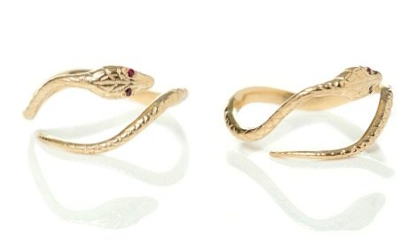 Antique-inspired Ouroboros snake ring in gold with ruby eyes.