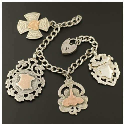 Antique sterling silver charm bracelet with antique medallions.