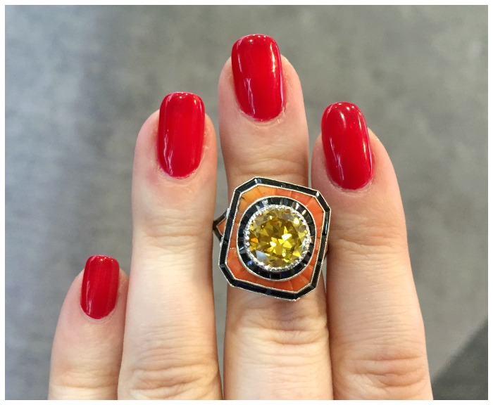 This ring features a 1920s Art Deco setting, inlaid with onyx and natural coral, and a 2.4 carat fancy brownish orangey yellow diamond. From Jogani.