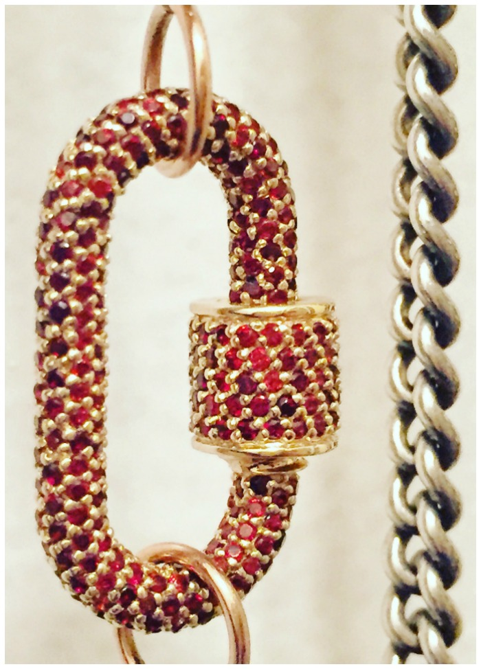 A Marla Aaron lock in gold with garnets on a heavy silver curb chain.