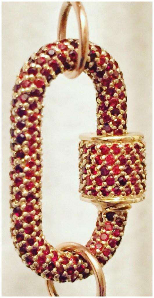 A Marla Aaron lock in gold with garnets.