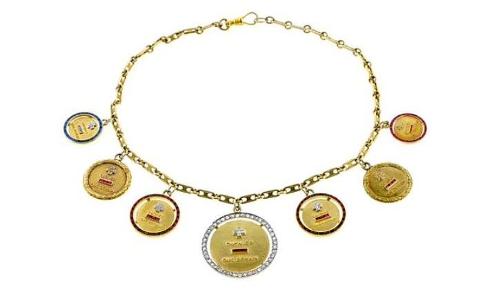 A charm necklace featuring seven individual Augis medaille d'amour charms. From the archive of Robin Katz Vintage.