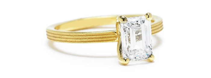 A Sholdt emerald-cut diamond engagement ring with fern finish in textured yellow gold.