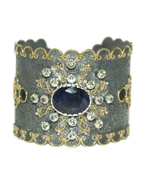 A sterling silver cuff bracelet by Stella Flame, with a sapphire and gold filigree.