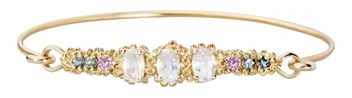 A beautiful handmade cuff bracelet by Ruta Reifen, with sapphires, rubies, and rainbow moonstone gemstones.