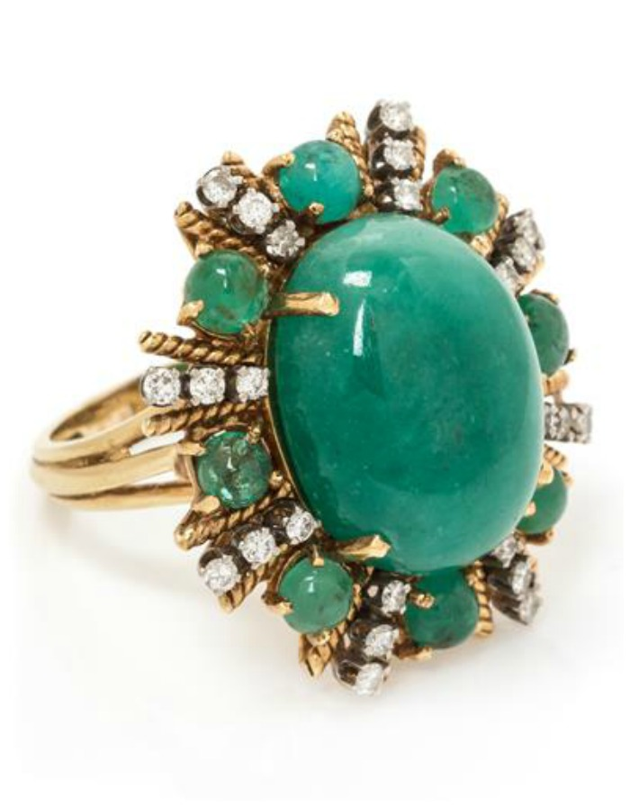 A fabulous vintage cocktail ring with a huge cabochon emerald surrounded by smaller emeralds and diamonds.