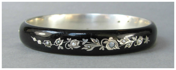 A Victorian silver and enamel mourning bangle with pearls.