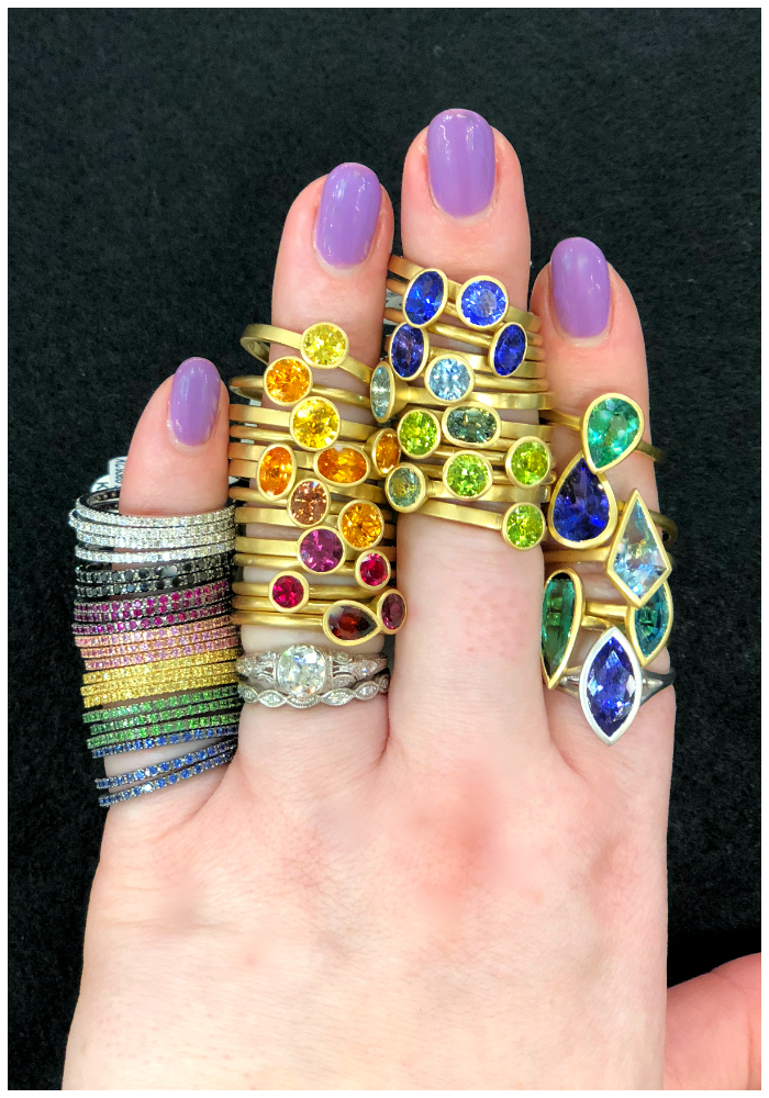 A rainbow of beautiful, bountiful, colored gemstone rings at Kimberly Collins Gems! I saw these at the 2018 AGTA GemFair.
