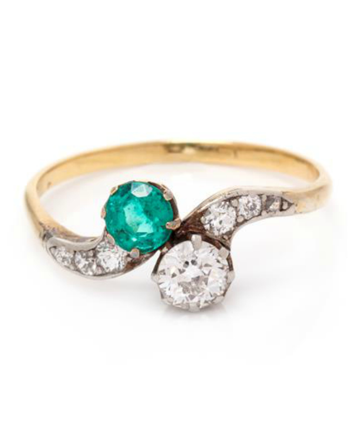 A beautiful Edwardian era moi et toi crossover ring with an emerald and diamonds.A beautiful Edwardian era moi et toi crossover ring with an emerald and diamonds.