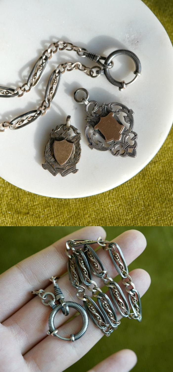 Two antique silver shield fob charms and a Victorian era Niello watch chain.
