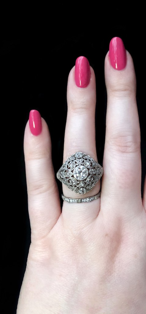 A stunning Edwardian era diamond ring; platinum-topped gold with filigree detailing. From Wilson's Estate Jewelry.