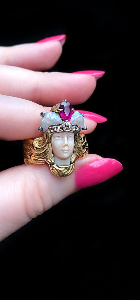 Incredible Art Nouveau era Empress ring from Wilson's Estate Jewelry. In gold, with opals and ruby. I love the details of her hair.