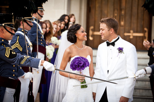 bride and groom walk down tunnel of swords