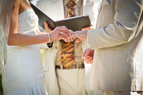 bride puts on grooms rign