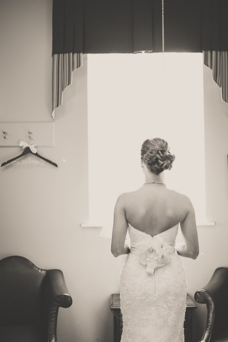bride standing in window light