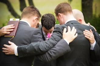 groom and grooms men huddled before wedding