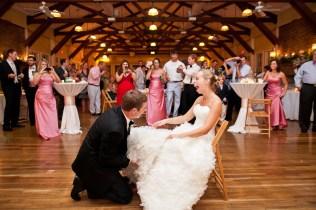 groom removing garter from bride's leg