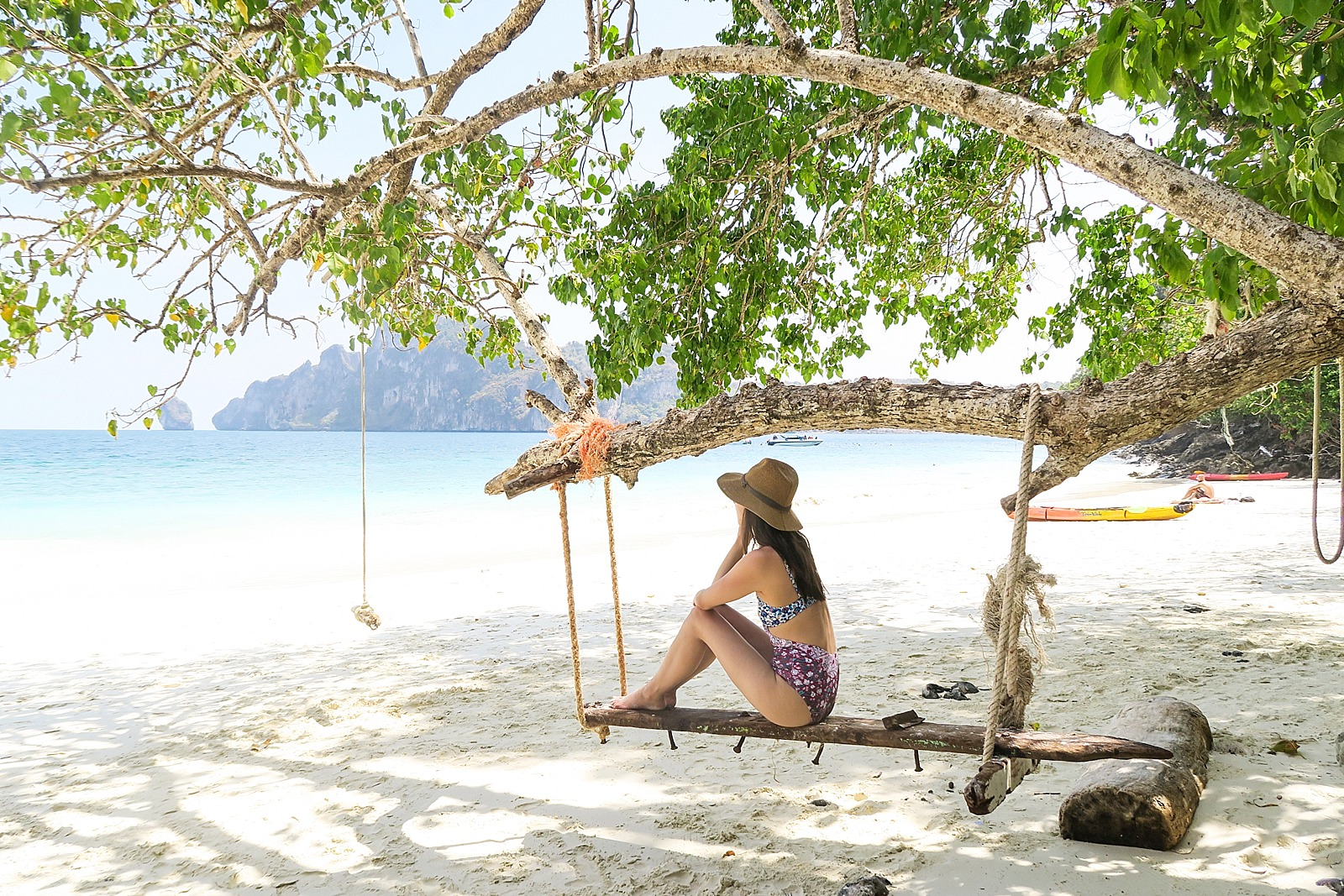 Diana Elizabeth lifestyle blogger travel sitting on monkey island in Thailand Phi phi islands wood bench swing under a tree