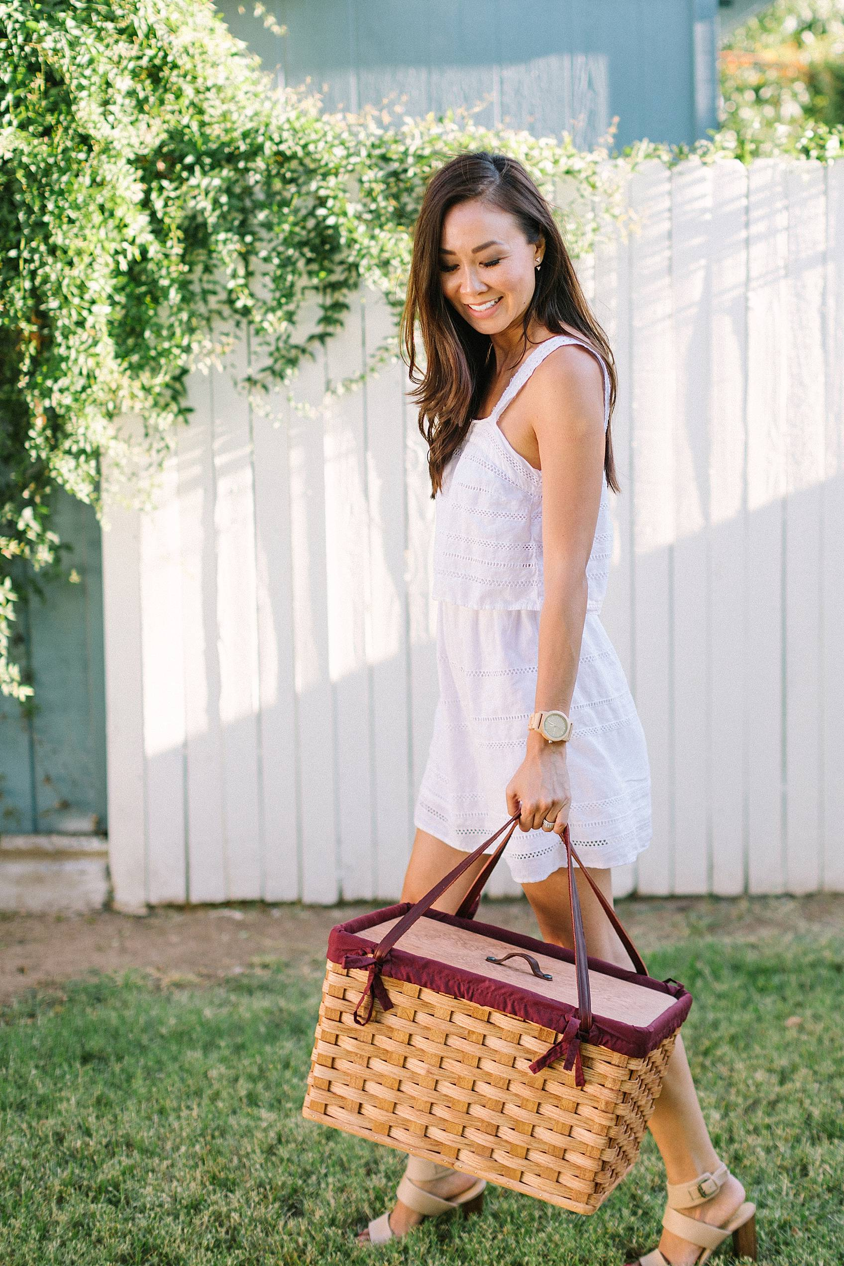 lifestyle blogger diana Elizabeth holding an amish made picnic basket in white dress infront of white fence standing on grass