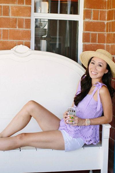 diana Elizabeth blogger on white bench holding lemonade