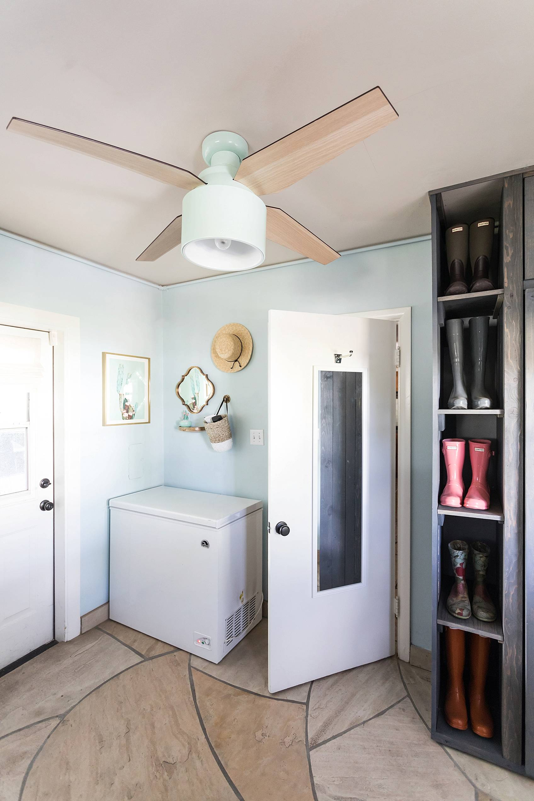 laundry mud room with custom cabinets rustic look with blue removable wallpaper in background and mint hunter fan