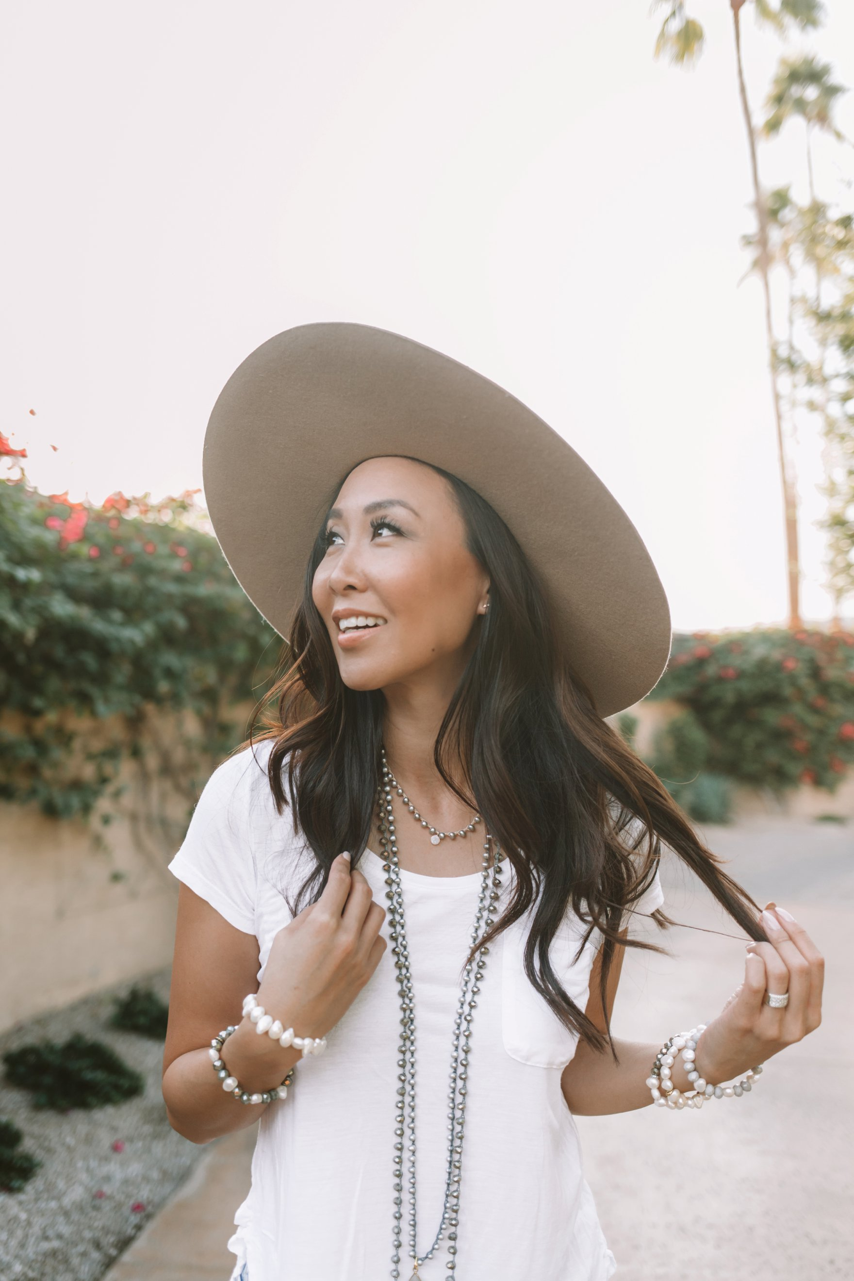 big felt hat with basic tee shirt and pearl necklaces. lifestyle style blogger Diana Elizabeth pulling strands of hair