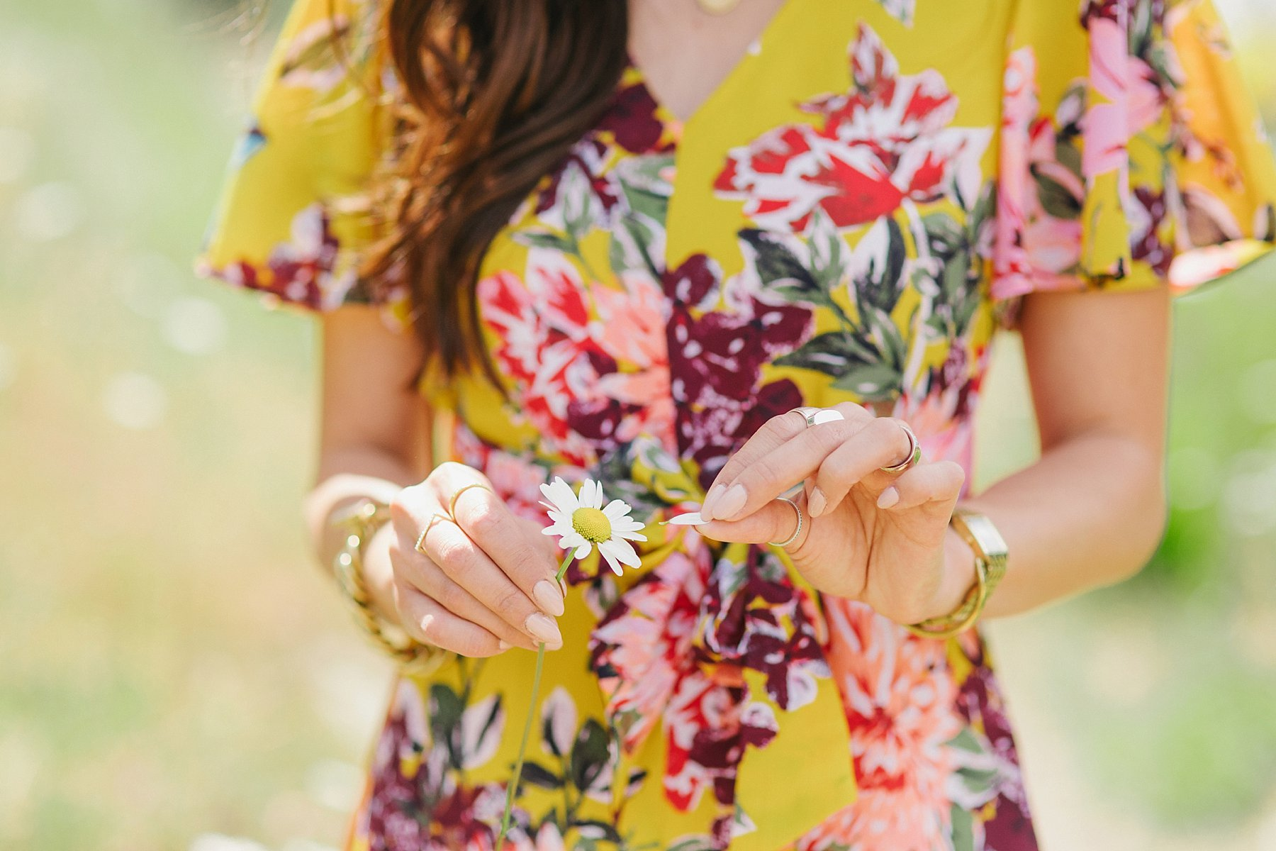 yellow floral jumpsuit by Tahari ASL on blogger Diana Elizabeth wearing straw boater hat and wicker tote standing in Bear Mountain in Victoria BC Canada - holding a daisy he loves me he loves me not