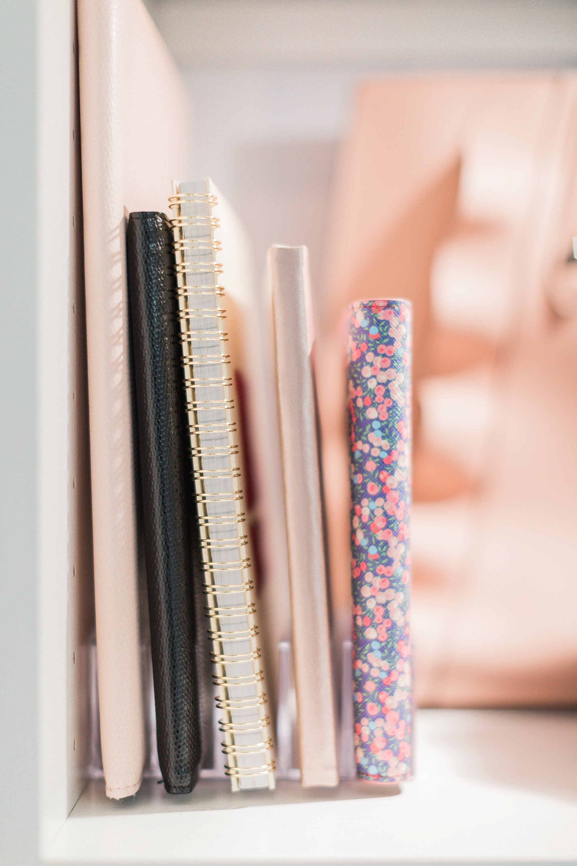 notebooks on hand in office closet: final reveal of office closet reveal belonging to photographer blogger Diana Elizabeth in phoenix arizona. created by California closets and with removable buffalo check wallpaper #office #closet #wallpaper #organization #lensorganization #lensdrawer