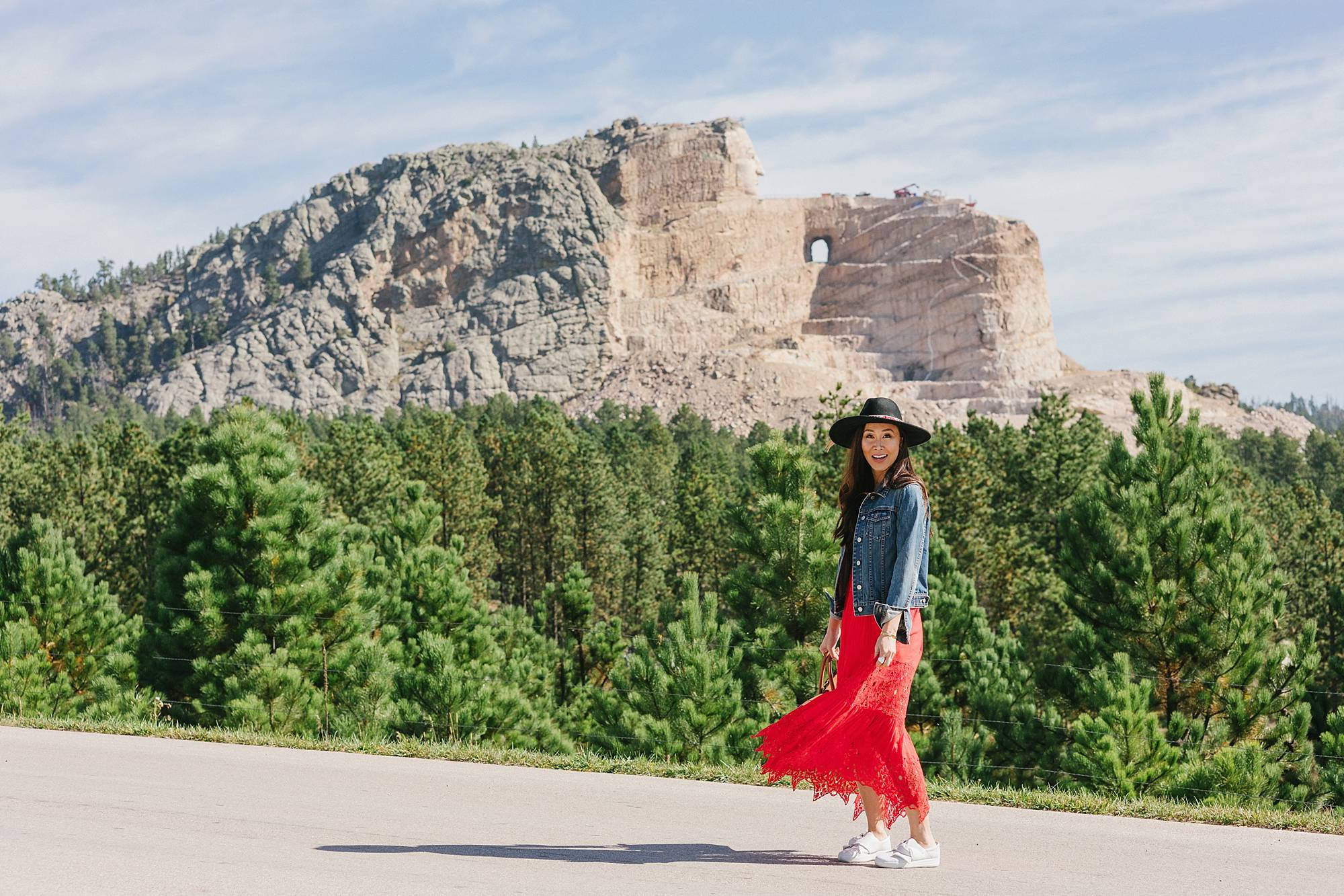 Crazy Horse Memorial in South Dakota - Diana Elizabeth Phoenix lifestyle blogger wearing red free people dress and wool hat and denim jacket posing and wearing white sneakers