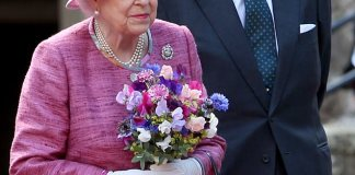 The Queen, dressed in a fuchsia coat and matching hat, with Prince Philip at the castle