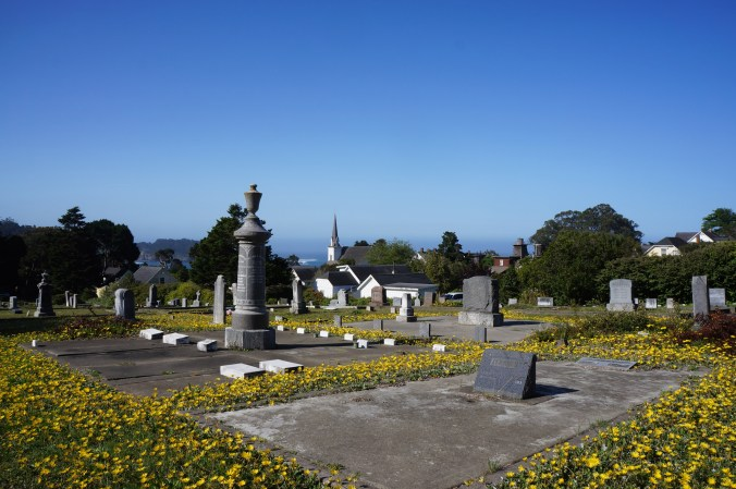 photograph of a cemetery on a hill overlooking the ocean