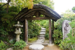 photograph of rock path in Japanese tea garden through a wooden gate flanked by two stone statues, one of a figure and one of a pagoda