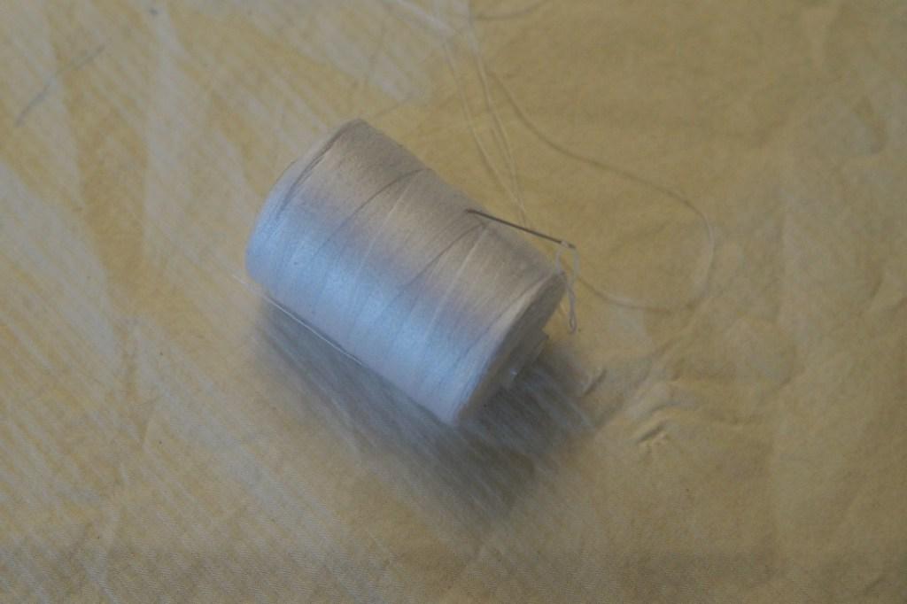 Nadel und Faden liegen auf einem Stück Stoff
