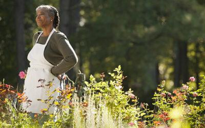 Mixed race woman wearing apron in field